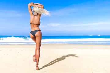 3D beautiful sun-tanned woman black swimsuit bikini on sea beach. Summer rest. Blue ocean background. Sunny day. Conceptual fashion art. Seductive candid pose. Realistic render illustration.