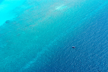 Aerial view over turquoise maldivian sea with boat