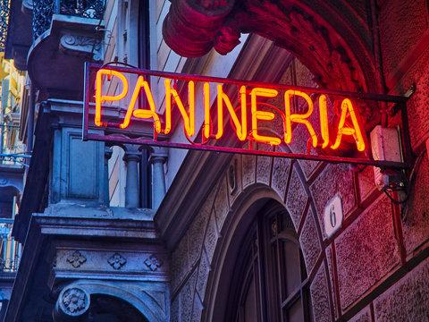 Panineria Neon signboard in an Italian street at nightfall.