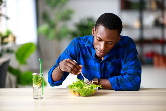 healthy eating. happy young black man eating salad in  morning in kitchen.