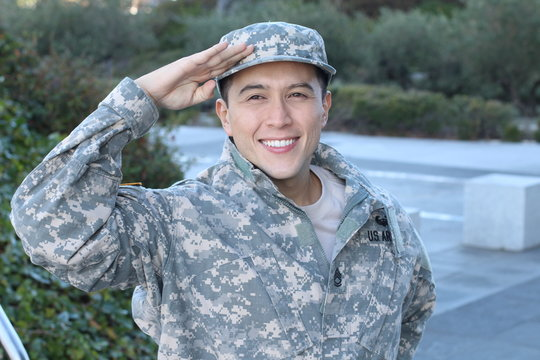 Cheerful young military soldier saluting