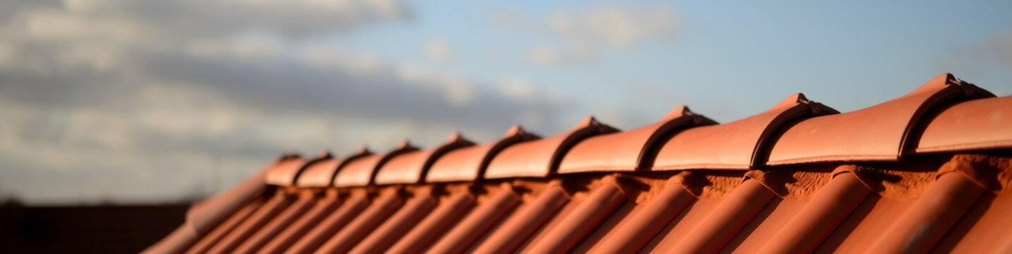 glänzend rote Dachziegel Pfanne vom Dachdecker Handwerker im Sonnenschein vor dunklem Hintergrund