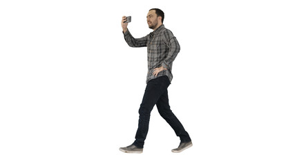 Young man taking photo with smartphone while walking on white background.