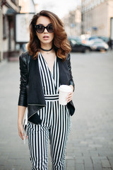 Seductive brunette woman wearing in black and white striped overalls and leather jacket, walking, posing at street, holding cup of coffee.Fashionable pretty girl with wavy volumed hair, in sunglasses.