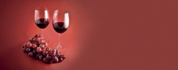 Red wine with grapes banner stock images. Burgundy autumn banner with wine. Two glasses of red wine. Red wine on a red background