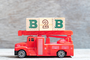 Red fire truck hold letter block in word B2B (abbreviation of business to business) on wood background