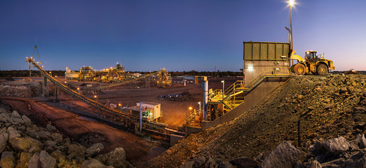 Bulldozer loading rocks into the crusher within the copper mine head at dusk in NSW Australia