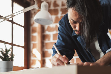 Young Asian man draft a drawing plan for artwork, architect, engineering drawing, creative designer concept