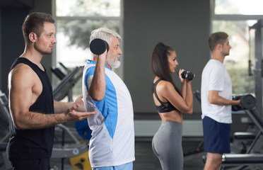 Fit people working out in modern gym with trainer.