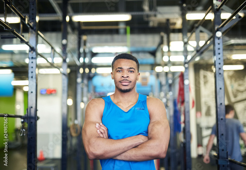 Young muscular athlete or sports coach with arms crossed on