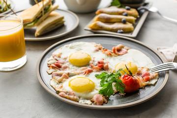 Breakfast, scrambled eggs, fruit, pancakes, orange juice, tea and sandwiches