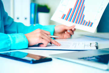 Business woman working with financial data holding sheet of paper with financial figures in hand and make notes in clipboard. Business financial and accounting concept.