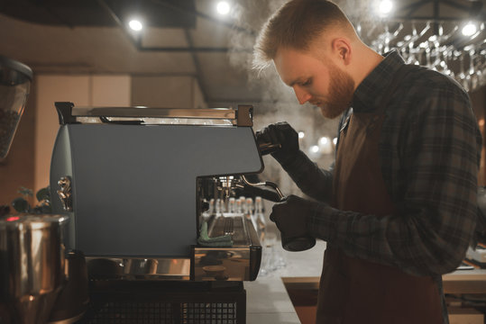 Barista steaming milk in pinscher. Portrait of bearded concentrated barista preparing cappuccino in a coffee shop. Cafe owner is focused on making coffee on a coffee machine.