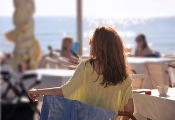 Beautiful woman sitting in a outdoor cafe at a beach resort