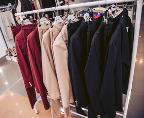 Rack with classic women's suits hanging on hangers in a clothing store