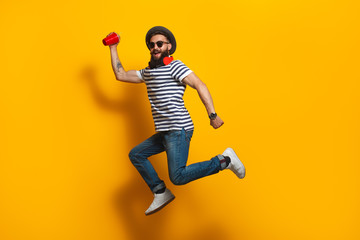 Jumping hipster with plastic cup