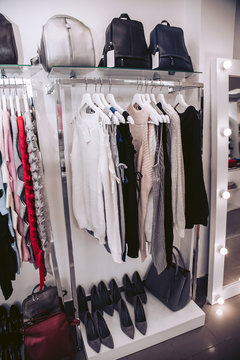 Showcases in the women's clothing store with luxurious dresses and shoes.