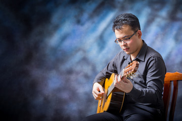 Portrait of asian man wearing playing guitar looking to the guitar and copy space