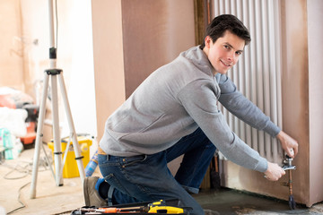 Portrait Of Male Plumber Fitting Vertical Radiator In Room Of House