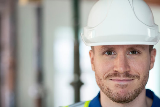 Portrait Of Male Construction Worker On Building Site Wearing Hard Hat