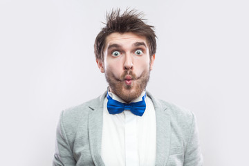 2ce2ad54f5be Closeup portrait of funny surprised handsome bearded man in casual grey suit,  blue bow tie