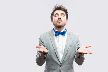 ad03fc3a5fdb Portrait of in love handsome bearded man in casual grey suit and blue bow  tie standing