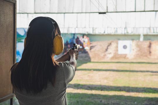 Young woman practice gun shoot on target