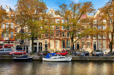 Fototapete - Channel of Amsterdam city. Netherlands. Motorboats by banks on Amstel river among trees and traditional dutch houses above water. Street with parked cars. Sunny spring day with blue sky.