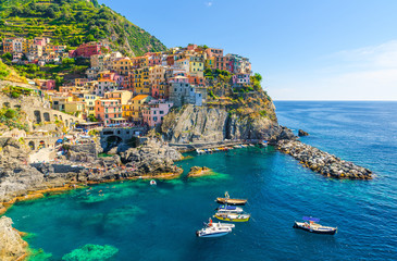 Manarola traditional typical Italian village in National park Cinque Terre, colorful multicolored buildings houses on rock cliff, fishing boats on water, blue sky background, La Spezia, Liguria, Italy Fototapete