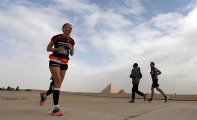 Runners participate in a marathon near the Pyramids of Giza