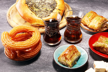 Middle eastern or arabic dishes and assorted meze, concrete rustic background. sambusak. Turkish Dessert Baklava with pistachio. Halal food.