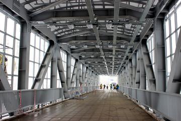 Metal construction, concrete floors, bridge. Supports are grey. Road.