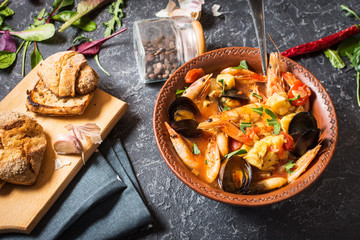 French fish soup Bouillabaisse with seafood, salmon fillet, shrimp, mussels on stone background. Delicious dinner Wall mural