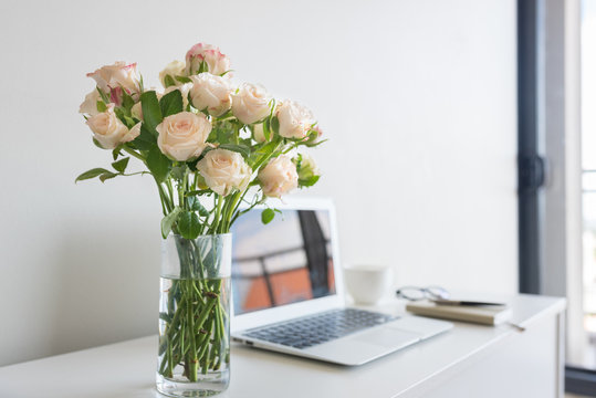 Close up of pale pink roses in glass with home office desk in background including, laptop, notebook, pen and glasses (selective focus)