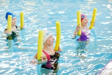 Side view at group of active senior women exercising in swimming pool, holding pool noodles and smiling, copy space