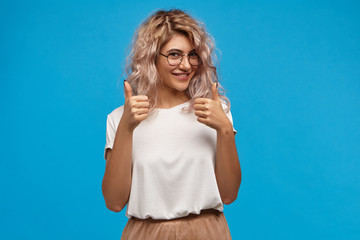 Cheerful hipster girl in trendy round eyewear making thumb up gesture with both hands and smiling joyfully, showing her support and respect to someone, saying Good job, Well done, I like that