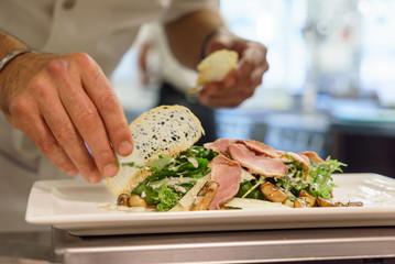 The chef prepares a dish in the kitchen of restorant