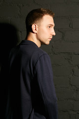 A young man in a blue jacket against a gray brick wall standing sideways
