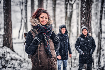 Red-haired student travels with friends in the Snowy forest