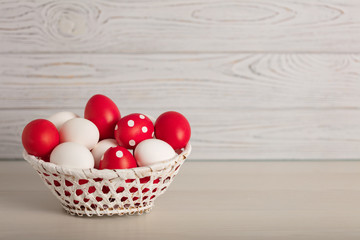 Happy Easter! Painted Easter eggs - red, white and red with white polka dots on a gray wooden...