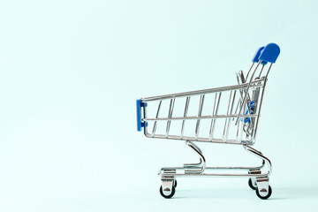 Discounts concept. Shopping cart  on a blue background with space for text