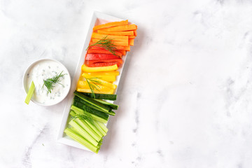 Colorful vegetable sticks with yogurt dip. Top view.