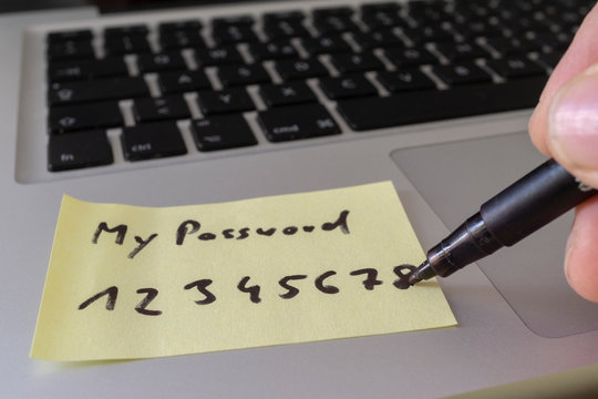 sticky note with weak easy password on laptop keyboard