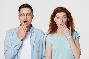 Shocked amazed couple covering mouth with hands looking at camera