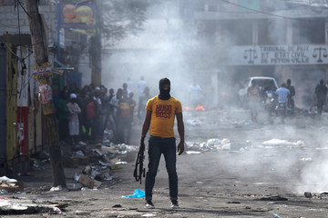 A man holds a weapon next to burning barricades during anti-government protests in Port-au-Prince