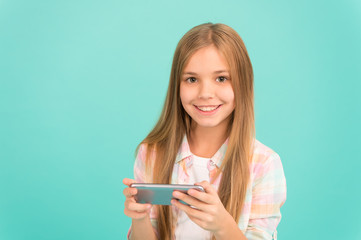 Problem of youth. Mobile phone and internet addiction. Addicted to internet online games. Mobile gadget dependence. Girl small child smiling hold smartphone. Internet surfing and social networks