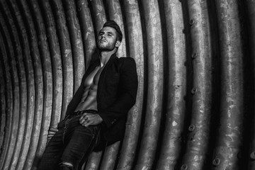 Muscular young man with beard on dark tunnel urban background. Fashion portrait of brutal strong muscle guy with modern trendy hairstyle. Model, fashion concept. Sexy naked torso. Black and white.