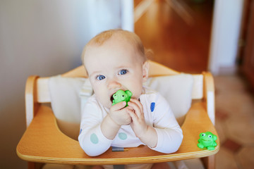 Baby girl sitting in high chair at home and playing with toys
