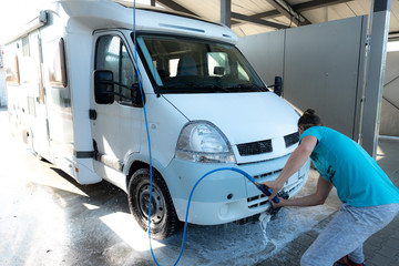 Man is cleaning his RV after a road trip in a car wash station