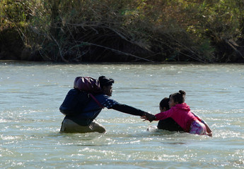 Migrants from Honduras try to cross the Rio Bravo towards the United States, as seen from Piedras Negras